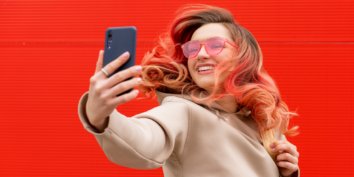 Woman making Instagram Reel with red background